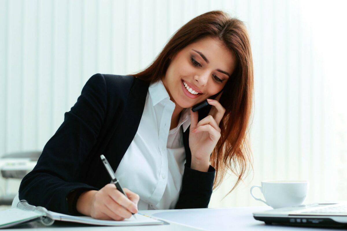 На фото – человек улыбается и разговаривает по телефону